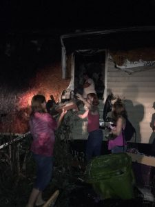 Photo courtesy of Katie Gunter Franklin : Family & friends help remove a baby bed made by the grandfather of Julie Gunter. It was one of the things they were able to recover from the fire.