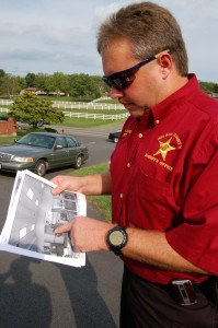 Nelson County Sheriff David Brooks examines surveillance imaages of the robbery suspect -- Photo by Tommy Stafford