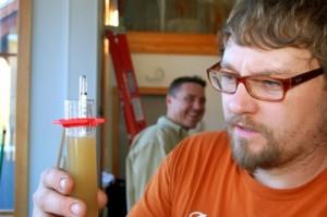 Jason checks sugar levels and viscosity of his brew.