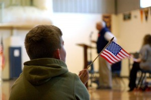 Photos By Tommy Stafford : A RRES youngster waves his American Flag as Veteran Paul Saunders of Piney River speaks in the background from the podium.