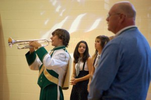 A trumpeter with the band plays taps to the crowd.