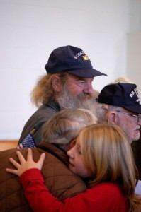 David Snyder from Nelson County, a U.S. Coast Guard veteran, looks on as a youngster hugs another vet at the RRES ceremony.