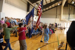 Students march out onto the gym floor with the American and Virgina State Flags.