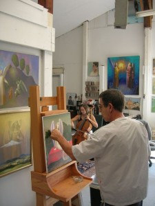 Photo By Tommy Stafford : Alexander Anufriev (left) works on a painting while wife and world-renowned cellist Tanya Anisimova practices on a musical selection.