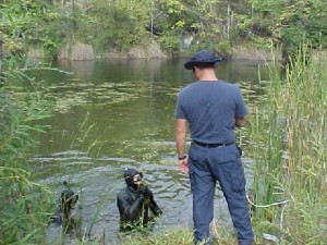 A diver coordinates with one of the crew on the bank.