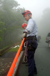 Rescue members pull tension on a rope and rigging used to pull a basket up from the mountainside overlook.
