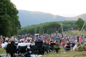 People gather, on what's normally a ski slope in the winter, just before dark in anticipation of the coming fireworks.
