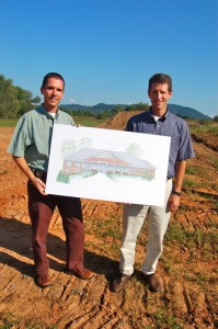 Dr. Charles Cole, (left) and Dr. Stephen Schmitz hold up a drawing of what the new clinic will look like once completed.