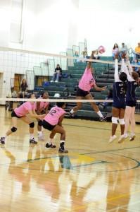 Erika Toliver, number 9 airborne in pink (Outside Hitter) attacks.