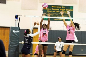 Keona Keona Loving (12) (Setter) and Maria McGarry (8) (Middle Blocker) defend against an attack.