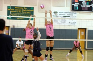 Natalie Campbell (13) (Defensive Specialist) and Madison Carter (7) (Middle Blocker) defend against an attack.