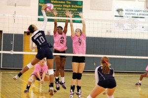 Keona Loving (12) (Setter) and Madison Carter (7) defend against an attack.