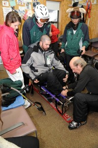 Clockwise from left to right Casey McInerny from Arlington, Virginia, Casper Cosmo from Stockholm, Sweden, Damion Armour from Wintergreen, Virginia, and Sam Shaver from Nellysford, Virginia, assist Michael Murphy from Arlington, Virginia into a mono-ski chair. Poles that assist with steering and braking are shown laying upon the blue chair.